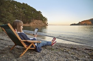 Woman works on HP Stream 8 tablet while sitting on the beach.